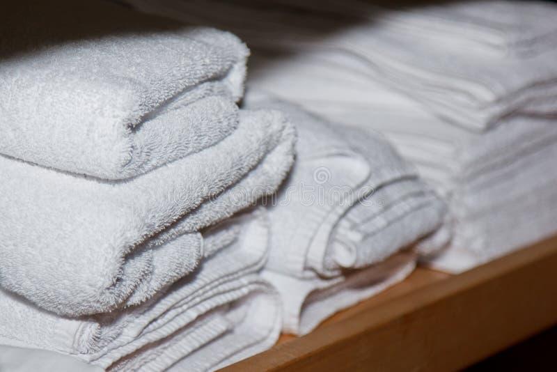 Gli asciugamani bianchi torti per i trattamenti della stazione termale sono sullo scaffale nella stanza di massaggio fotografie stock libere da diritti