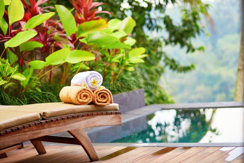 Gli asciugamani con il frangipane bianco fiorisce vicino allo stagno immagine stock
