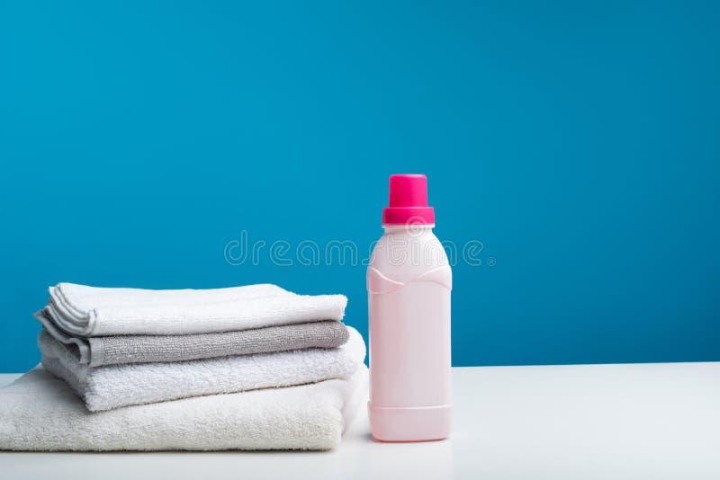 Gli asciugamani di bagno hanno piegato vicino alla bottiglia dell'emolliente immagini stock