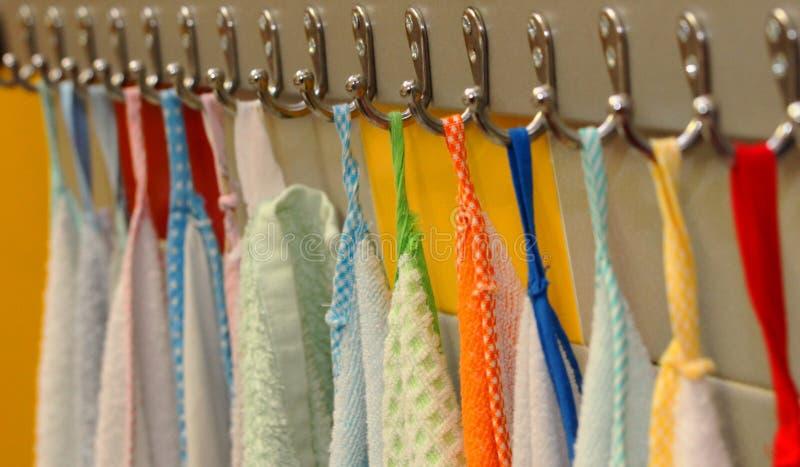 Gli asciugamani hanno appeso sui ganci del metallo nel - Nel bagno della scuola ...