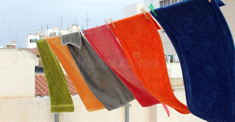 Gli asciugamani variopinti sono appesi e mossi dal vento fotografia stock