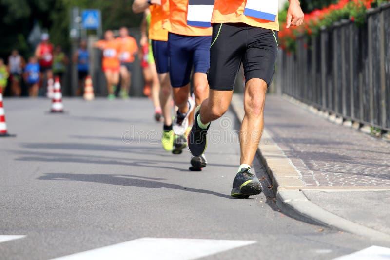 Gli atleti funzionano nella via nella città fotografia stock libera da diritti