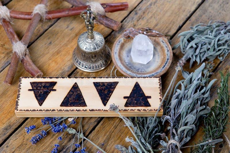 Gli elementi - terra, fuoco, acqua, aria con la campana d'ottone, cristallo di quarzo, pentagramma del ramo e pacchi delle erbe s immagine stock