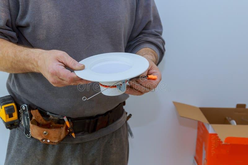 Gli elettricisti economizzatori d'energia stanno sostituendo come luce economizzatrice d'energia del LED di installazione immagini stock