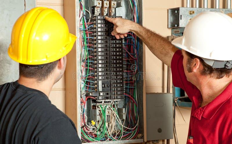 Gli elettricisti sostituiscono un interruttore da 20 ampère fotografia stock