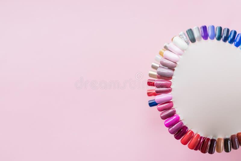 Gli esempi dei chiodi fornisce di punta sulla vista superiore del fondo di rosa pastello Colori luminosi moderni di modo del mani fotografie stock