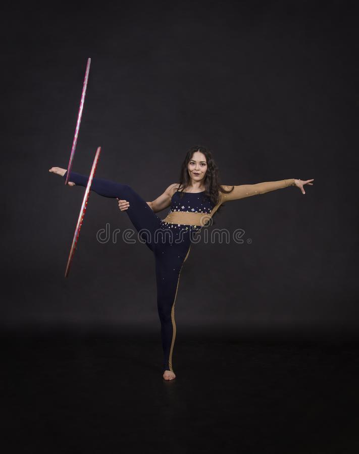 Gli esercizi relativi alla ginnastica con la ragazza del hula-hoop esegue un artista del circo immagini stock