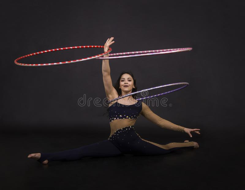 Gli esercizi relativi alla ginnastica con la ragazza del hula-hoop esegue un artista del circo fotografie stock