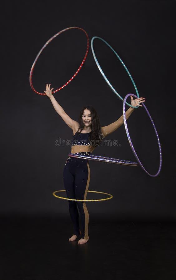 Gli esercizi relativi alla ginnastica con la ragazza del hula-hoop esegue un artista del circo fotografia stock