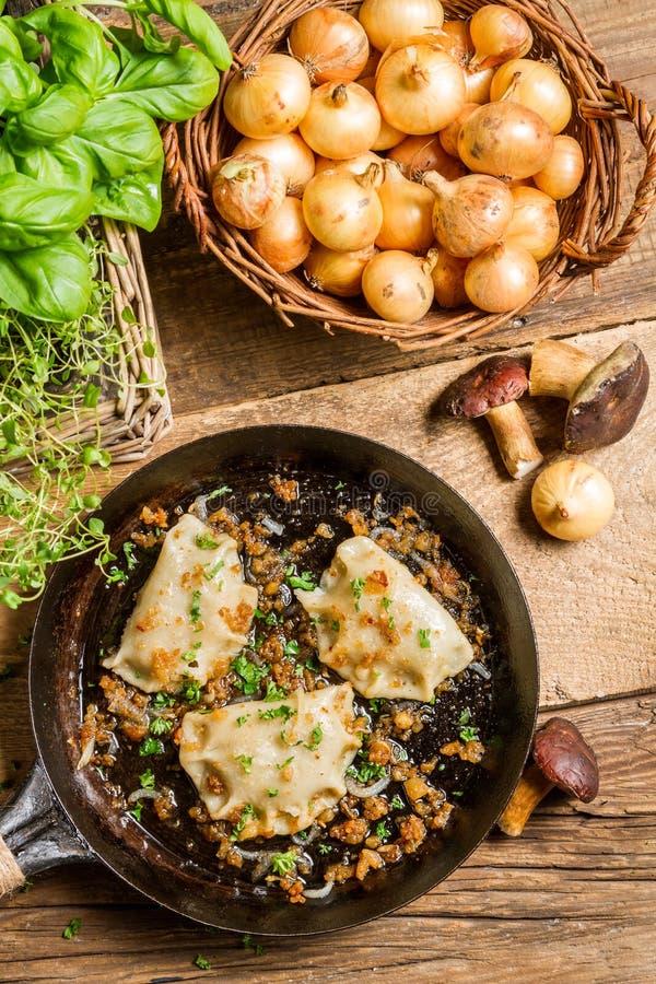 Gli gnocchi casalinghi con i funghi hanno fritto con la cipolla ed il prezzemolo immagine stock
