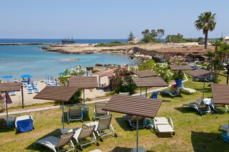 Gli hotel tirano con acqua del turchese del mar Mediterraneo con la barca e gli alberi immagini stock