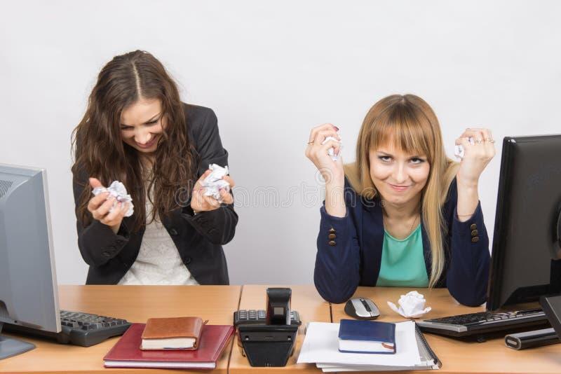 Gli impiegati dell'ufficio furioso sgualciscono la carta fotografia stock