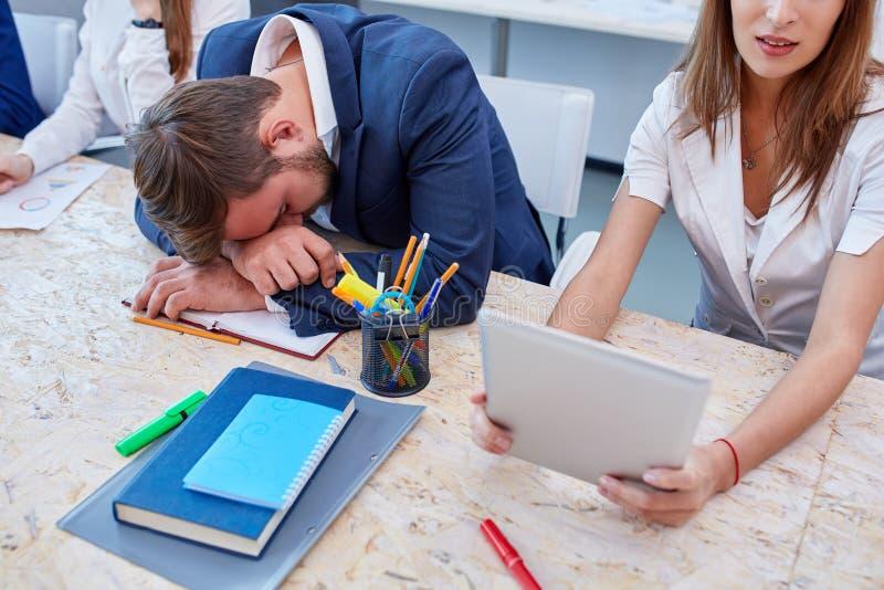 Gli impiegati di concetto nel processo del lavoro, l'uomo sono caduto addormentato alla tavola immagine stock