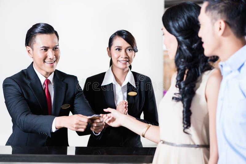 Gli impiegati di un hotel accoglie favorevolmente le giovani coppie fotografia stock libera da diritti