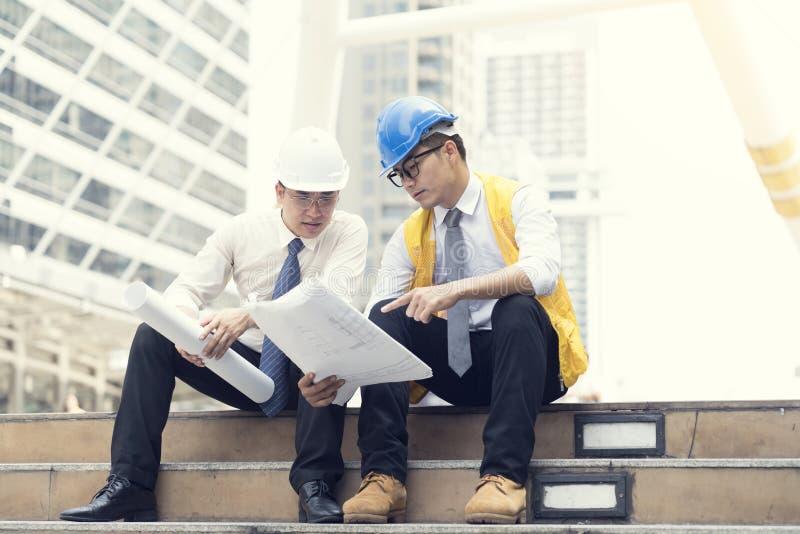 Gli ingegneri asiatici sono stati consultati insieme e progettano nella costruzione immagine stock libera da diritti