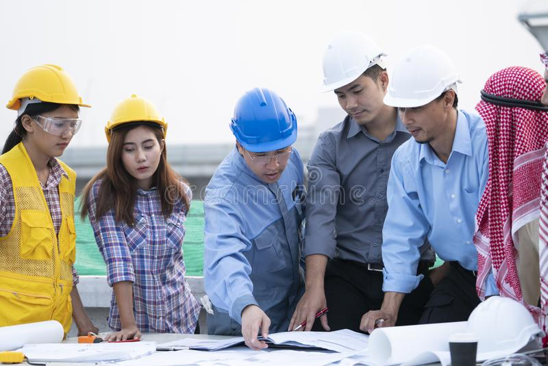 Gli ingegneri asiatici sono stati consultati insieme e progettano nella costruzione fotografia stock
