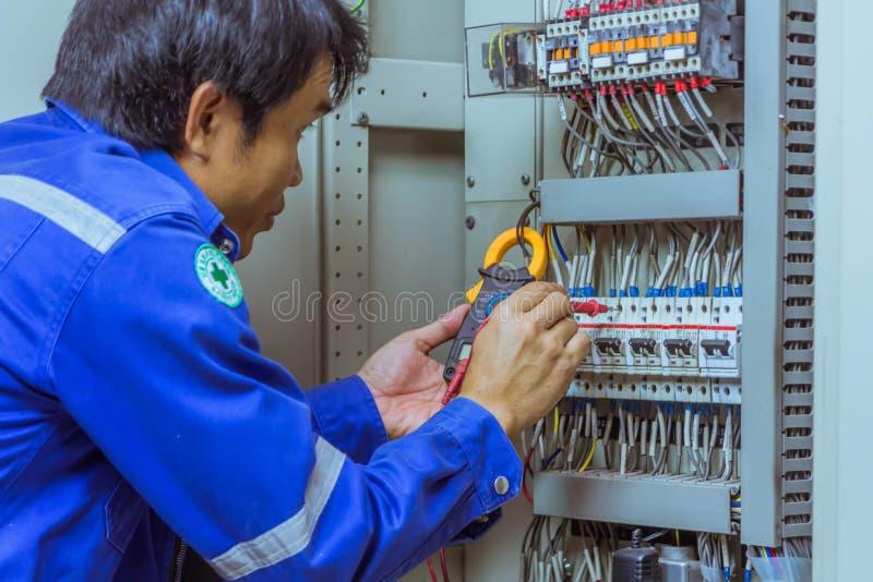 Gli ingegneri maschii stanno controllando il sistema elettrico con il electroni immagini stock