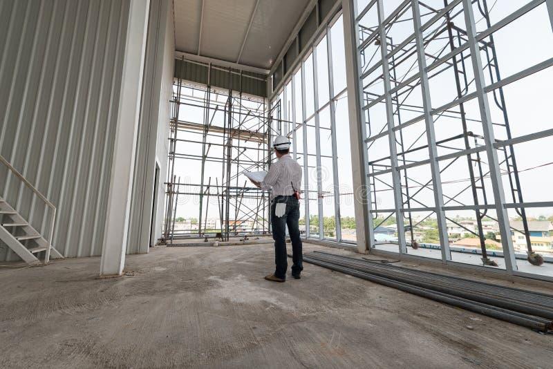 Gli ingegneri maschii stanno stando la costruzione in costruzione di modello dell'orologio fotografia stock