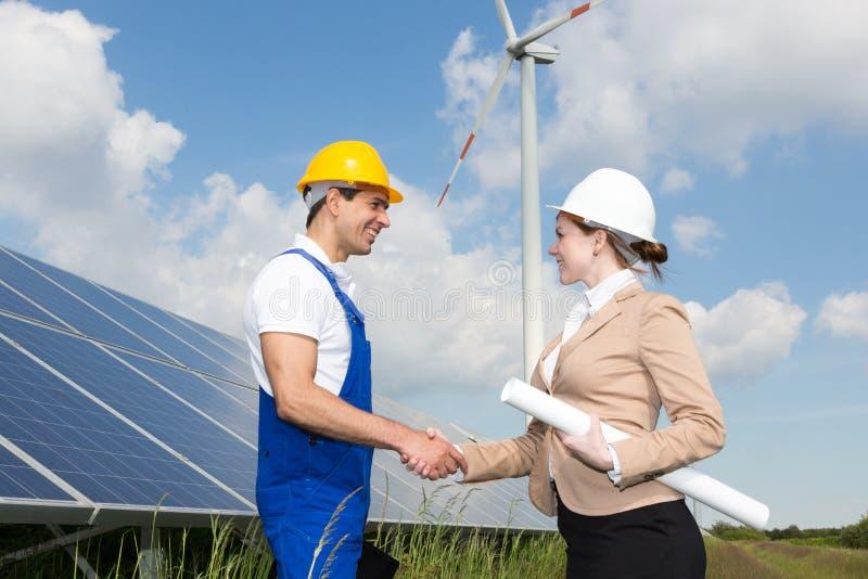 Gli ingegneri stringono le mani davanti ai pannelli solari ed al generatore eolico fotografie stock