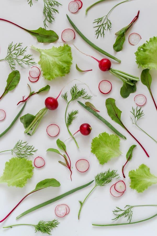 Gli ingredienti dell'insalata si situano pianamente Verdure organiche sulla a su un fondo bianco fotografie stock