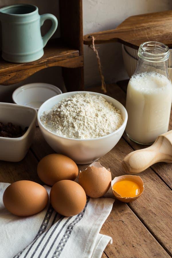 Gli ingredienti di cottura flour, uova, il tuorlo aperto, il latte, il matterello, l'armadietto, l'uva passa, l'interno rustico d fotografia stock libera da diritti
