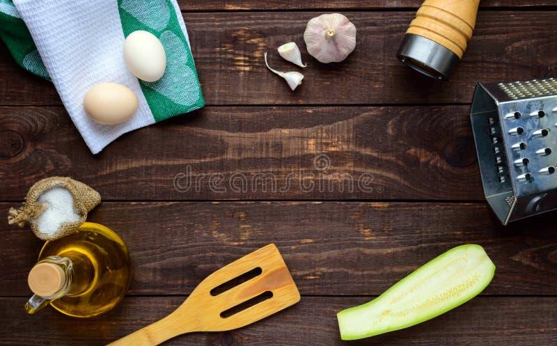 Gli ingredienti e gli strumenti per la cottura dei pancake dallo zucchini su un fondo di legno scuro immagine stock libera da diritti