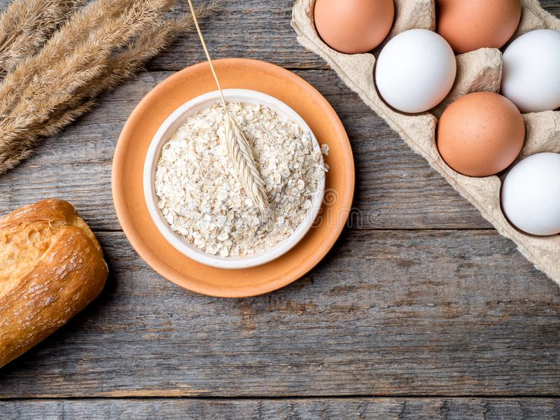 Gli ingredienti per le uova della farina d'avena della prima colazione impanano lo spazio di legno rustico della copia del fondo  immagine stock libera da diritti