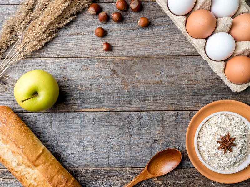 Gli ingredienti per le uova della farina d'avena della prima colazione impanano lo spazio di legno rustico della copia del fondo  fotografia stock