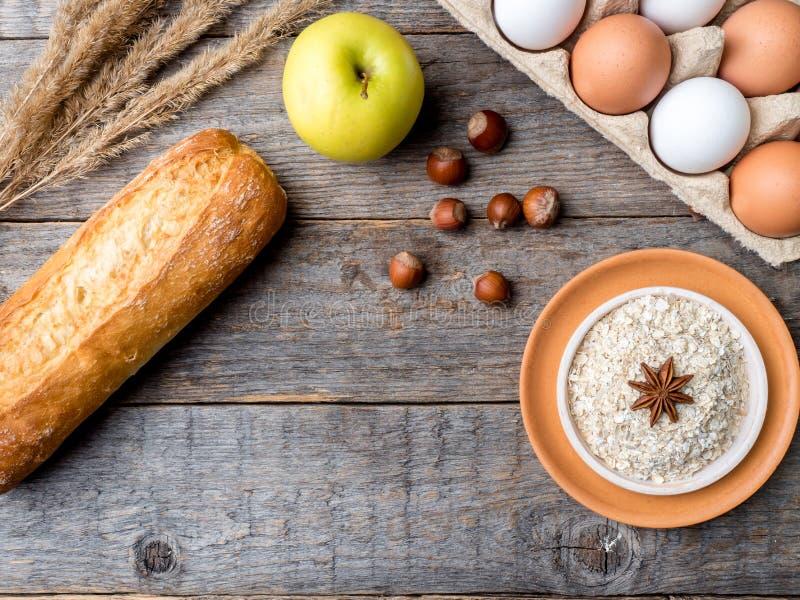 Gli ingredienti per le uova della farina d'avena della prima colazione impanano lo spazio di legno rustico della copia del fondo  fotografia stock libera da diritti