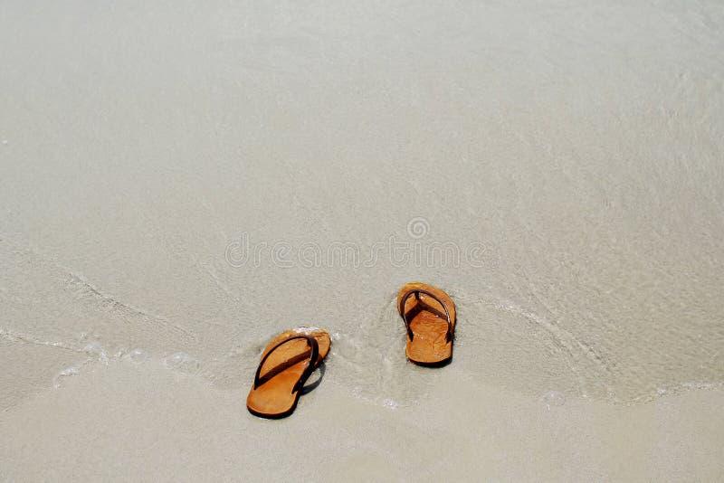 Gli inizio dell'estate decolliamo il vostro sandalo quindi vada al mare, fotografie stock libere da diritti