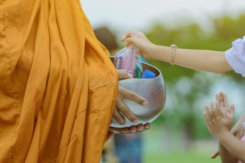 Gli insegnanti e gli studenti fanno insieme il merito per dare le offerti dell'alimento ad un monaco buddista i giorni religiosi  immagine stock