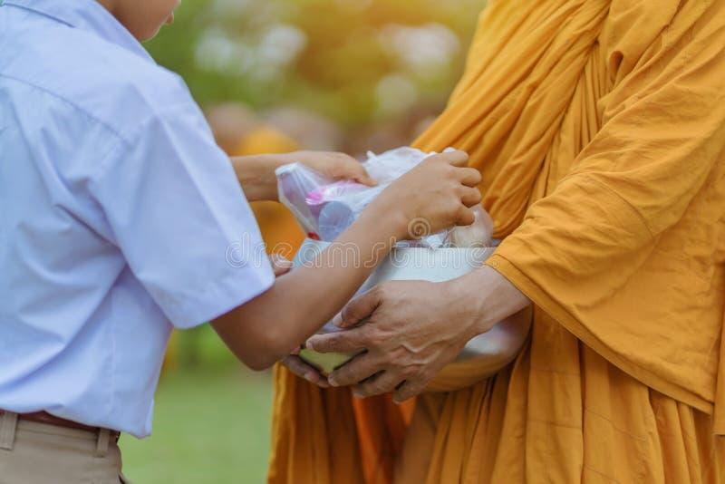 Gli insegnanti e gli studenti fanno insieme il merito per dare le offerti dell'alimento ad un monaco buddista i giorni religiosi  fotografie stock libere da diritti
