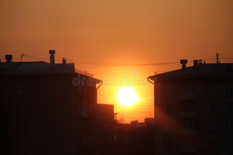 Gli insiemi del sole fra le case fotografia stock libera da diritti