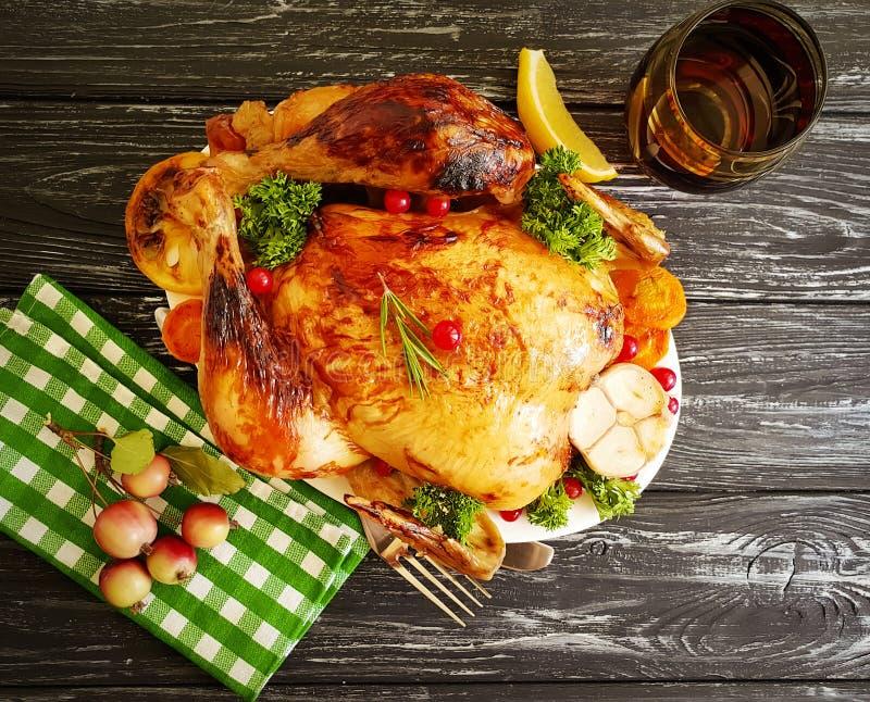 Gli interi rosmarini del pollo fritto hanno lustrato pronto, saporito cucinato su fondo di legno fotografia stock
