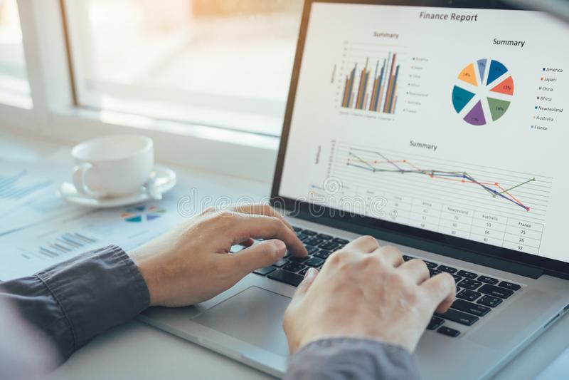 Gli investitori stanno utilizzando i computer portatili per analizzare i grafici di mattina immagine stock