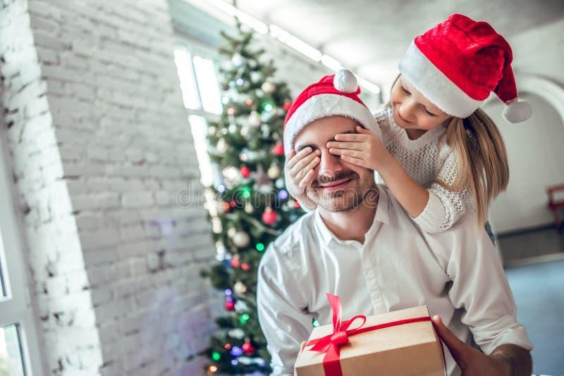 Gli occhi del padre di chiusura della figlia allegra sveglia con la mano che dà il contenitore di regalo fotografia stock libera da diritti