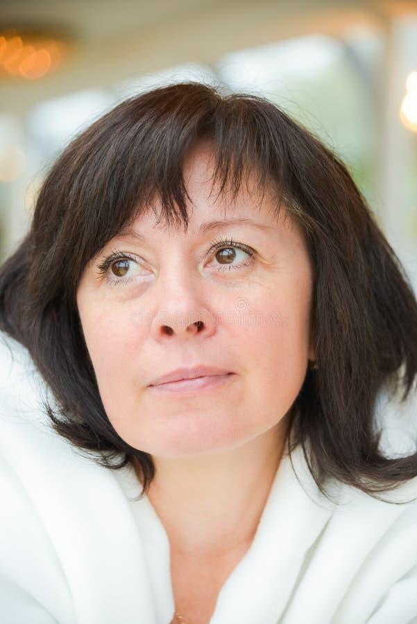 Gli occhi di mezza età di marrone della donna sta sedendosi nell'appartamento fotografia stock libera da diritti