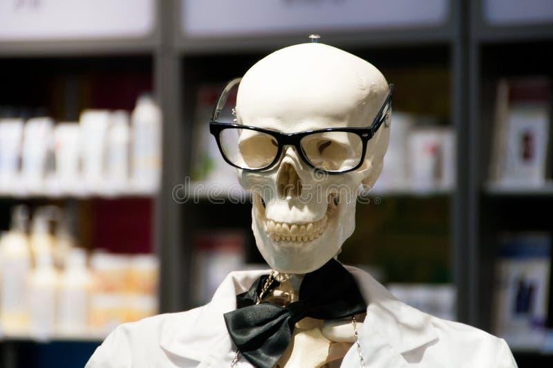 Gli occhiali d'uso capi del cranio ed il laboratorio scientifico bianco ricoprono fotografie stock libere da diritti
