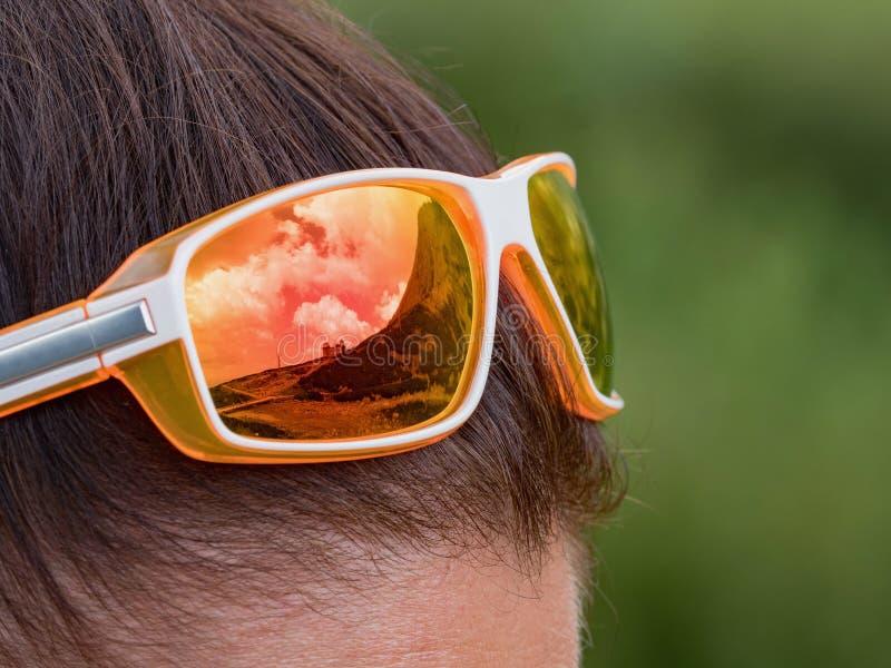 Gli occhiali da sole arancio sul ` s della ragazza si dirigono Gli specchi di vetro i dintorni di alto Tatras in Slovacchia fotografia stock libera da diritti