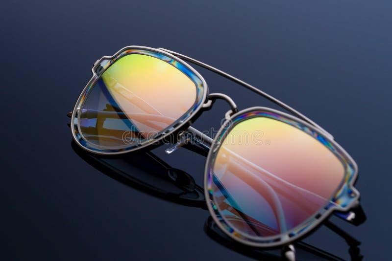 Gli occhiali da sole, colore del camaleonte, luccicano al sole Fondo scuro di pendenza fotografie stock libere da diritti