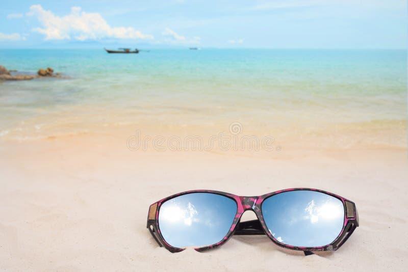 Gli occhiali da sole di viaggio di festa sulla spiaggia di sabbia e sul sole riflettono immagine stock libera da diritti