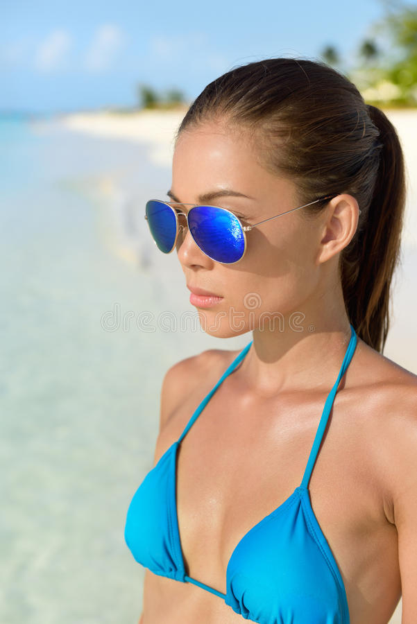 Gli occhiali da sole tirano la donna in secco asiatica con il bikini blu sexy immagini stock