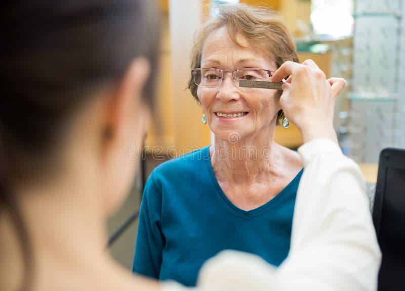 Gli occhiali di Measuring Woman femminile dell'ottico fotografie stock