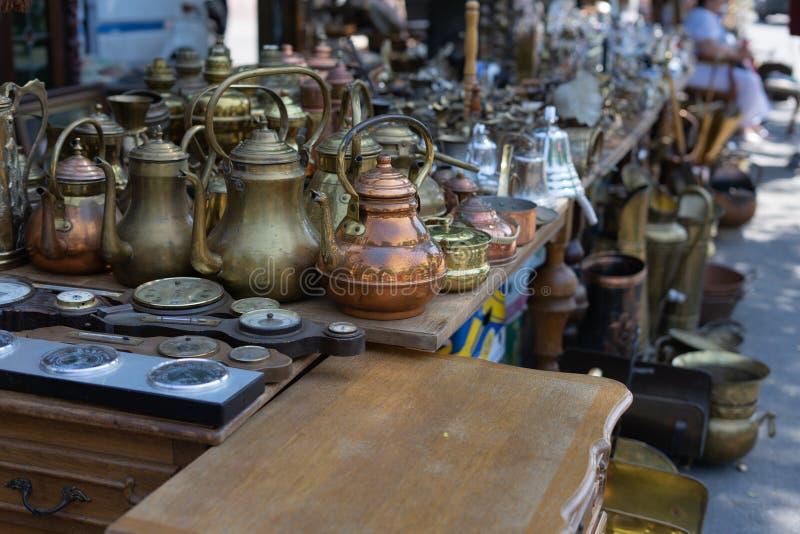 Gli oggetti d'antiquariato antichi sono venduti ad un mercato delle pulci Turchi del caffè e bollitori di rame fotografia stock libera da diritti