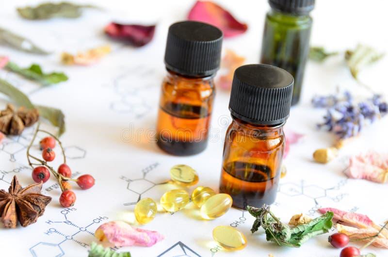Gli oli essenziali con le erbe ed il supplemento su scienza rivestono immagine stock libera da diritti