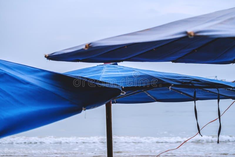 Gli ombrelli di spiaggia sul mare ondeggia il fondo immagine stock