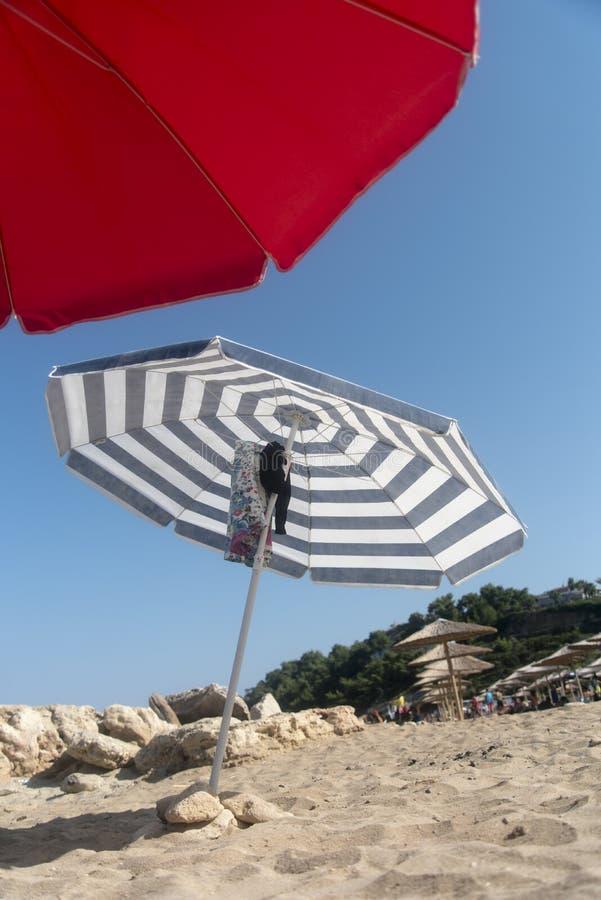 Gli ombrelli impilano sulla sabbia immagine stock libera da diritti