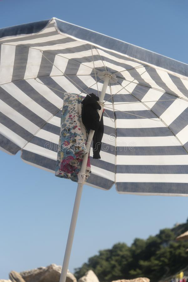Gli ombrelli impilano sulla sabbia fotografie stock