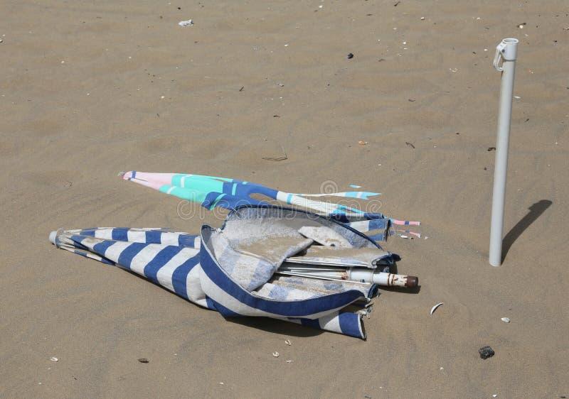 Gli ombrelloni sulla spiaggia è sommerso dalla sabbia dopo il tornad fotografie stock