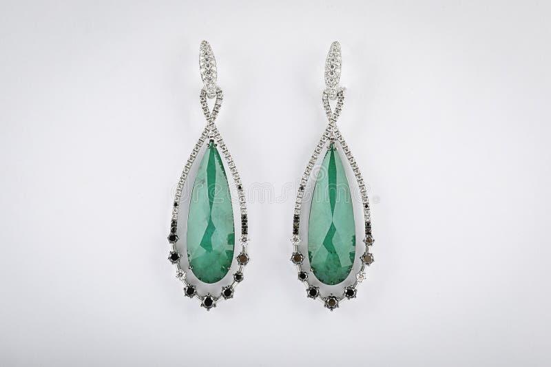 Gli orecchini d'argento delle donne con i diamanti, pietra verde nel mezzo sotto forma di una goccia, isolata su un fondo bianco fotografia stock libera da diritti